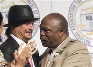 Rev. Wendell Anthony embraces Kid Rock, who used Confederate flags on stage during his performances.