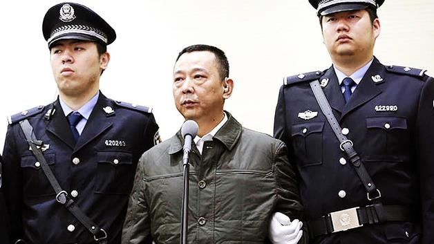 Corbis: Shen Zhengyi, ImagineChina/Liu Han, center, former chairman of mining conglomerate Sichuan Hanlong Group, is held by police officers during a trial at the Xianning Intermediate Peoples Court in Xianning city, central Chinas Hubei province, 31 March 2014