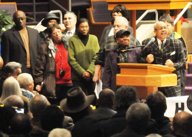 Rev. Pinkney (r) speaks at first mass rally against Emergency Manager Law Public Act 4, later repealed and replaced with PA 436. Rally of thousands was held at New Triumph Baptist Church in Detroit.