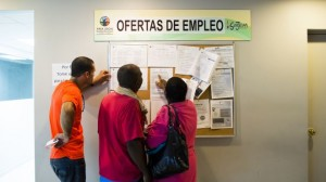 Unemployed Puerto Rican workers check job board.