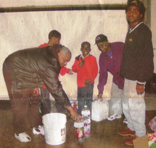 Frank Lewis delivers water to his neighbors, 10 year old Edward Jones, 6 year old Pierre Cook and their parents Marilyn Cook and Edward jones during wave of water shut-offs in 2002.