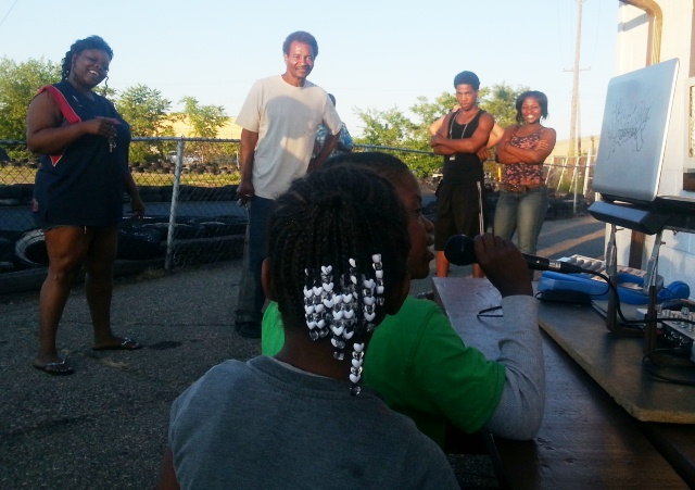 Ron Hereford, proprietor of Doll's Go Kart, (above center), and Jamar Reed's family and friends watch him sing for a ride.