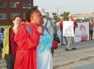 Jean Vortkamp is at left behind Monica Patrick (in red jacket) during blockade of Homrich water shut-off facility July 18, 2014.