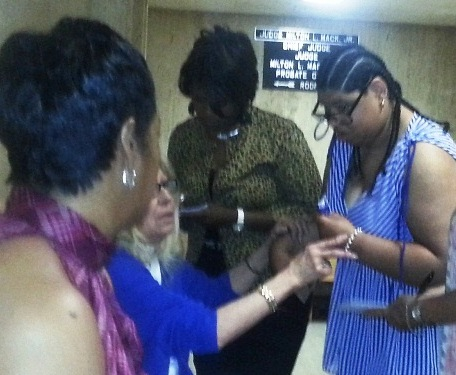 Atty. Mary Rowan (seated in blue) grabs Mailauni Williams' arm outside court June 13, 2013. The next day Rowan seized the young woman; her whereabouts are now unknown to her family.