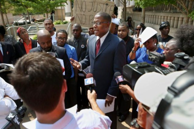 Malik Z. Shabazz, president and founder of Black Lawyers for Justice based in Washington, D.C., holds a news conference in front of the federal courthouse in St. Louis on Thursday, Aug. 28, 2014 where he announced the details of a $40 million lawsuit his organization filed against police and the governments of Ferguson and St. Louis County. The lawsuit alleges that police in Ferguson and St. Louis County used excessive force and falsely arrested innocent bystanders amid attempts to quell widespread unrest after the fatal shooting of a black 18-year-old by a white police officer. (AP Photo/St. Louis Post-Dispatch, David Carson)