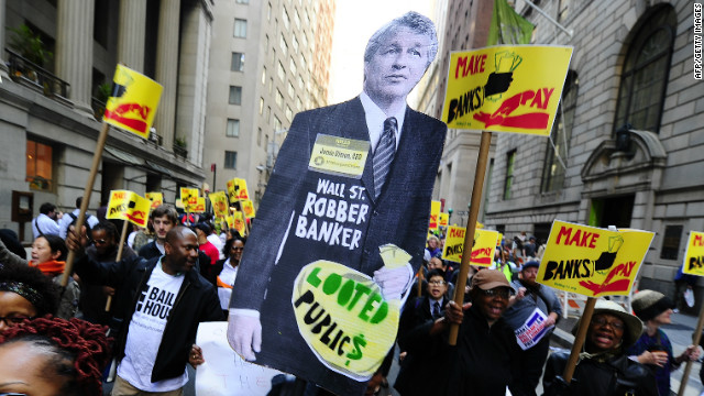 Protesters carry large sign with Chase CEO Jamie Dimon depicted as robber banker.