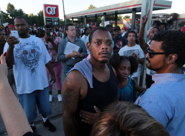 "I am out here to stand up for my children,"" said Terrell Williams El of Ferguson, who holds his daughter, Sharell, 9, close as he confronts police officers in riot gear during a protest along West Florissant Rd. on Wednesday, Aug. 13, 2014, in Ferguson. Photo by Laurie Skrivan, lskrivan@post-dispatch.com"