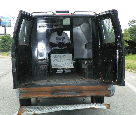 "Baxter Jones, in battered police truck, proclaims ""Beat Back the Bullies."""