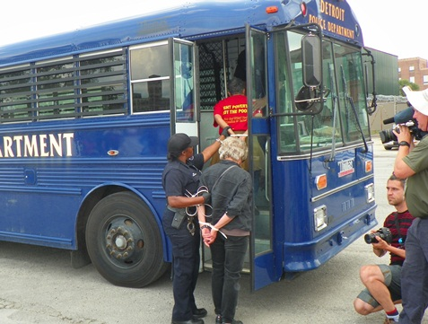 "Marian Kramer (in red T-shirt proclaiming ""Fight Poverty, Not the Poor,"" is arrested and put on police bus."