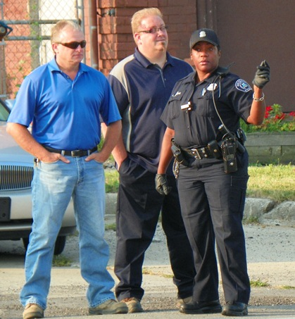 Homrich CEO Roger Homrich (center) with facility boss at left and police officer.