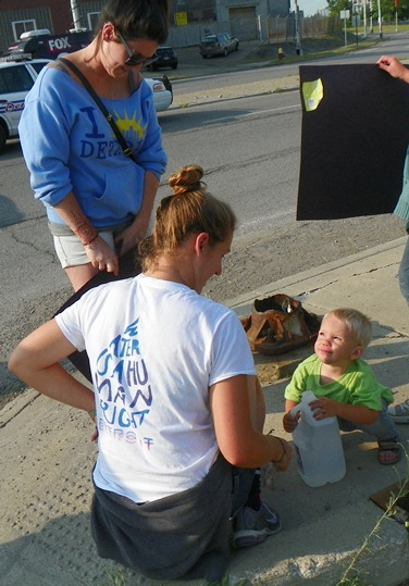 Child protester smiles at mom as he quenches thirst on Homrich blockade July 18, 2014.