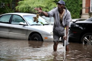 Larry Young of Highland Park tries to clean out his storm drain during Detroit flood, coming up with handful of contaminated sewage. Photo:DFP