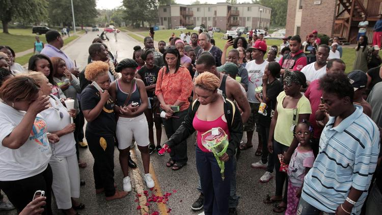 (Huy Mach / St. Louis Post-Dispatch) Lesley McSpadden, center, drops rose petals on the bloodstains from her son, Michael Brown, 18, who was shot dead by police in Ferguson, Mo.