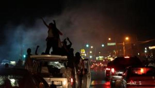 Police, protesters clash for a sixth night in Ferguson, MO Aug. 15, 2014, angry at attempts to criminalize Michael Brown.