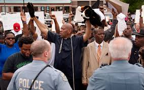 Protesters raise hands, imitating Michael Brown's stance while a Ferguson, MO police officer shot him to death, causing outrage in the community,