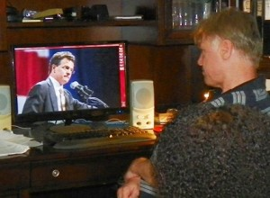 Scheid watches U.S. Congressional Candidate David Trott, owner of the largest foreclosure mill in the region, on video.