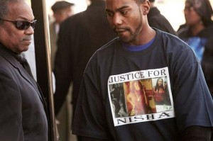 "Friend attends McBride's funeral wearing ""Justice for Nisha"" T-shirt. She was a graduate of Southfield High School and an employee of Ford Motor Company."