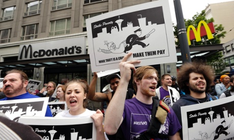 In this Aug. 1, 2013 photo, demonstrators protesting what they say are low wages and improper treatment for fast-food workers stand near a McDonald's restaurant in downtown Seattle.