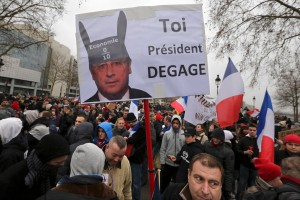 "A demonstrator holds up a sign portraying French President Francois Hollande wearing donkey ears with a school grade of Zero and which reads, ""You, President Resign."" Photo: Reuters"
