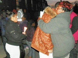 Woman comforts grieving youth during the vigil.