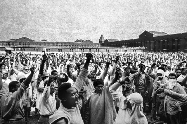 This Sept. 10, 1971 file photo shows inmates of Attica State Prison as they raise their hands in clenched fist salutes to voice their demands during a negotiating session with New York's prison Commissioner Russell Oswald. AP File Photo