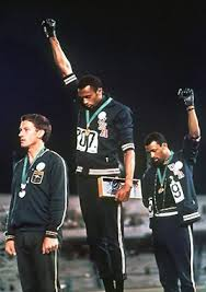 Gold medallist Tommie Smith, (center) and bronze medalist John Carlos (right) showing the raised fist on the podium after the 200m race in the 1968 Summer Olympics. Australian medalist Peter Norman stood with them in solidarity.