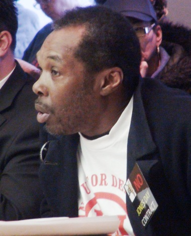 "Speaker at Detroit City Council, wearing ""NO JONES DAY"" opposes hiring of firm April 9, 2013. A strong campaign was waged by hundreds of Detroiters to stop the contract. Jones Day previously represented the State of Michigan to engineer the bankruptcy."