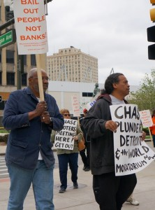 Abiyomi Azikiwe of Moratorium NOW! and Bill Davis, Pres. of the Detroit Active and Retired Employees Association, marched on Chase meeting. In background is Kris Hamel of Moratorium NOW! telling Chase to leave Detroit. /Photo: Stephanie Gordon