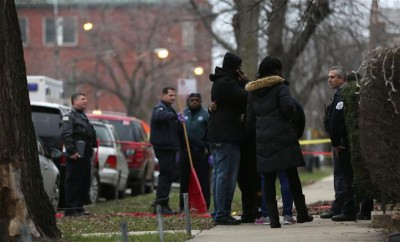 Chicago police officers talk with relatives of one of the two people killed by a police officer.