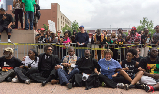 Cornel West (third from l) and others engage in civil disobedience outside federal courthouse in St. Louis. West and others were later arrested. FC photo