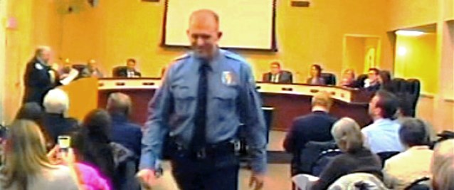 In this  Feb. 11, 2014 file image from video provided by the City of Ferguson, Mo., officer Darren Wilson attends a city council meeting in Ferguson.