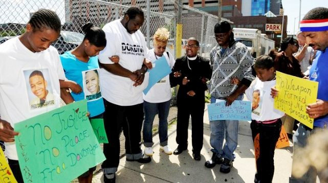 Davontae's mother, Taminko Sanford-Tilmon, with his stepfather and family, pray for his release outside the Frank Murphy Hall, where Kym Worthy's offices are located, in 2012.