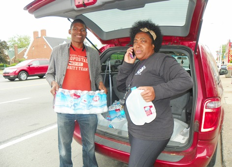 Demeeko Williams and Beulah Walker load water to carry to two Detroit residents, one a senior whose water has been shut off for a year, and another a young woman with a child who has been forced to squat in a Detroit home. Gallons of water are given out freely, with no questions asked.