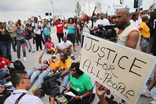 Demonstrators in Ferguson, MO, site of police execution of Michael Brown,