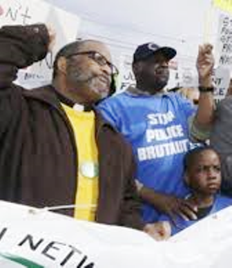Father Ellis Clifton (l)protests with Floyd Dent and grandson at head of march April 2, 2015.