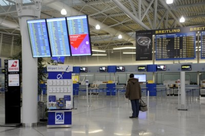 A passenger looks at an announcement board inside the Athens Eleftherios Venizelos International Airport, as flight controllers hold a work stoppage during a 24-hour general strike against planned pension reforms in Thursday. (Michalis Karagiannis/Reuters)