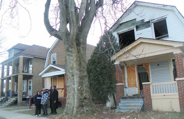 (L to r) Luis and Cecilia Mendoza, with Cornell Squires, point out abandoned, burnt out properties next to their home (at far left). They have paid $16,000 in property taxes but are facing foreclosure March 31. They have five children.