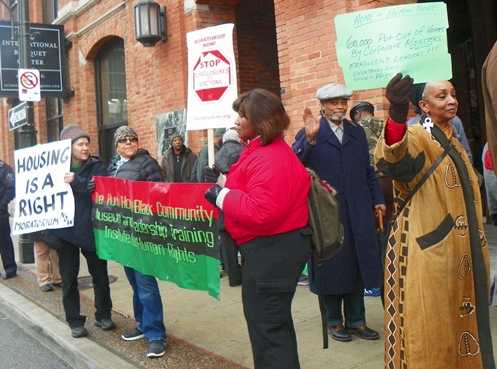 Dr. Sandra Simmons (r) and Prof. Charles Simmons (in cap) of HUSH House join protest: HOUSING IS A HUMAN RIGHT!