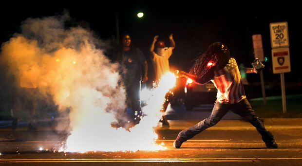Young demonstrator in Ferguson throws tear gas canister back at riot troops after killing of 18-year-old Michael Brown. His killer, Darren Wilson, is scott free.