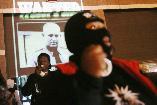 Ferguson demonstrators outside police station with photo of Mike Brown's killer, cop Darren Wilson, projected on wall Nov. 21, 2014. Photo: Scott Olsen/Getty