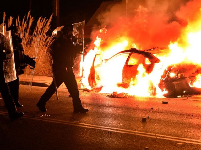 Ferguson police car burns Nov. 24 after grand jury verdict announced.