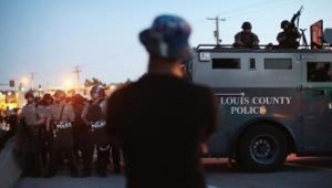 Militarized police patrol streets of Ferguson after Michael Brown's murder.