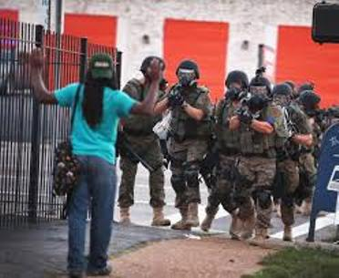 Paramilitary police confront lone youth during Ferguson uprising.