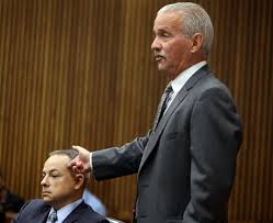 Defense attorney Steve Fishman repeatedly mocked Ms. Jones' allegation that Weekley put his gun to Aiyana's head, as he demonstrates here with Weekley. Wayne Co. ME Carl Schmidt's testimony, however, left that possibility open,