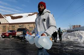 Flint resident carries jugs to obtain clean water. Former Detroit City Councilwoman Sheila Cockrel told Detroiters whose water had been shut off due to inability to pay to go to the Detroit River and get their water there.