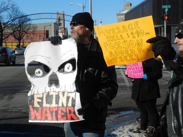 Protesters at Flint city hall in January. Flint's Emergency Manager ordered the city to disconnect from the Detroit Water & Sewerage Dept. and establish its own water treatment facilities. Residents have since complained of  polluted water, higher rates.