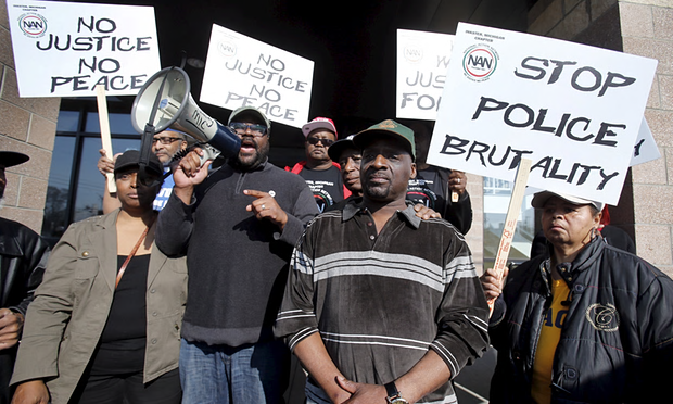 Floyd Dent (center) participates in protest outside the Inkster Police Department. Photo: Reuters/The Guardian