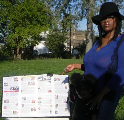 Protester Harris points to lengthy list of police killings of Detroiters displayed at Lamar's memorial Sept. 21, 2016.