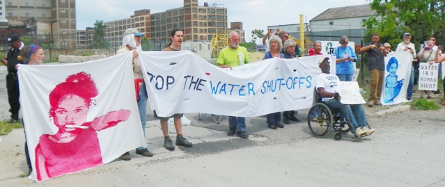 Protesters ready themselves for arrest as they block the entrance to contractor Homrich to stop water shut-offs July 18, 2014. Activist Baxter Jones, at right, was first to be taken.
