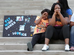 Ikeila Watford, cousin of teenager Andre Green who was shot by IMPD Sunday night, sheds a tear as his aunt Chonda Watford and sister Terika Jackson mourn the loss of his life on Monument Circle during a vigil held Monday evening, August 11, 2015.(Photo: Matt Detrich/The Star)